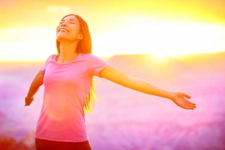 Gelukkige mensen - vrije vrouw genieten van de natuur zonsondergang. Vrijheid en sereniteit concept met vrouwelijk model in extatisch. Gemengd ras Aziatische Kaukasische vrouwelijke model in 20 genieten van zonsondergang, Grand Canyon, USA