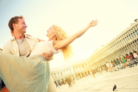 travelling: Romantic couple in love having fun embracing and laughing in Venice, Italy on Piazza, San Marco  Stock Photo