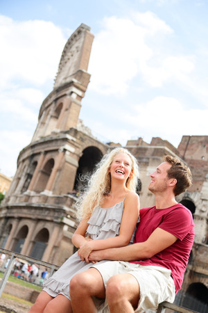 Tourist couple in Rome by Coliseum on travel dating laughing having fun