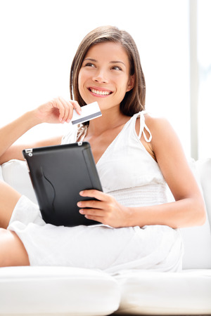 Pretty asian caucasian woman shopping on online on internet using tablet computer with credit card in hand.  photo