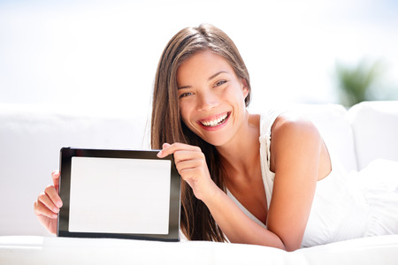 Tablet computer. Woman showing blank empty screen with copy space.  photo