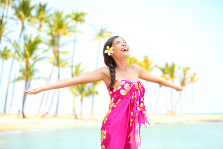Happy woman praising freedom smiling on hawaiian palm beach in sarong, arms stretched out. Beautiful mixed race female model enjoying sun in worship and meditation zen. Big Island, Hawaii, USA. photo