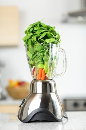 믹서에 녹색 야채 스무디. 집에서 부엌에서 믹서 스무디 준비 시금치, 셀러리, 당근 등의 야채와 함께 건강 식품 개념.