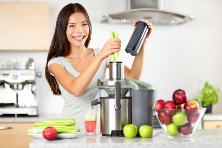Vegetable juice raw food - healthy eating woman with juicer juicing green vegetables and apple fruits as part of her wellness food. Beautiful happy mixed Asian woman with juice maker in kitchen. Stock Photo