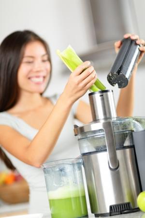 verduras verdes: Jugo de vegetales - mujer jugos vegetales verdes en la m�quina licuadora o exprimidor. Concepto sano de los alimentos crudos con la persona que hace el zumo de apio de verduras en la cocina. Centrarse en el apio. Foto de archivo