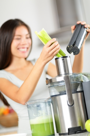 raw food: Vegetable juice - woman juicing green vegetables on juicer machine or juice maker. Healthy raw food concept with person making celery vegetable juice in kitchen. Focus on celery.