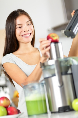 Woman making apple and vegetable juice on juicer machine at home in kitchen. Juicing and healthy eating happy woman making green vegetable and fruit juice. Mixed race Asian Caucasian model. Stock Photo