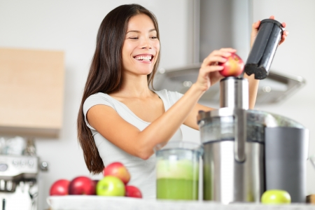 Juicing - woman making apple and green vegetable juice using juicer machine at home in kitchen. Healthy eating happy woman making green vegetable and fruit juice. Mixed race Asian Caucasian model. photo