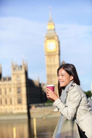 London woman drinking coffee happy by Big Ben laughing. Young female professional on Westminster Bridge, London, England. Beautiful young multiracial Asian Caucasian girl. photo
