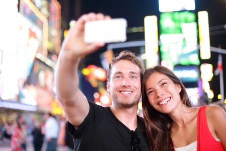 Dating young couple happy in love taking selfie self-portrait photo on Times Square, New York City at night. Beautiful young tourists having fun date, Manhattan, USA. Asian woman, Caucasian man