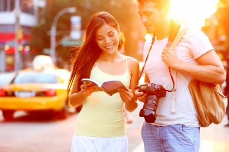 Pareja de turistas de viajes de viaje en Nueva York el libro guía de lectura de pie con cámara réflex al atardecer en Manhattan con taxi amarillo en el fondo. Feliz pareja multirracial joven en vacaciones de verano