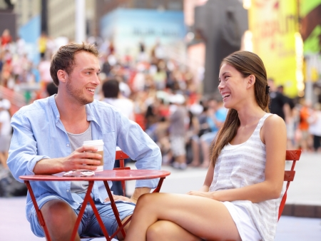 Dating couple, New York, Manhattan, Times Square dating drinking coffee smiling happy sitting at red tables enjoying their tourism vacation travel in the USA. Asian woman, Caucasian man. Stock Photo