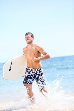 Summer beach fun surfer man running with bodyboard. Fit fitness model doing water sport bodyboarding surfing. Photo from Kaanapali beach, Maui, Hawaii. photo