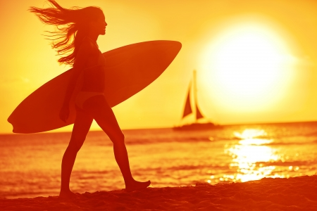 surfing: Surfing surfer woman babe beach fun at sunset. Girl walking in sunshine in warm evening sun holding surfboard. Water sport summer vacation travel concept. Kaanapali beach, Maui, Hawaii, USA