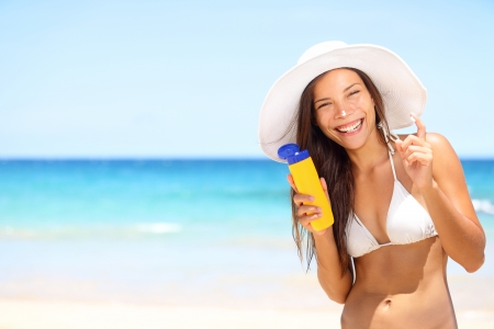 Sunscreen beach woman in bikini applying sun block solar cream for UV protection. Girl smiling to camera, wearing white sun hat, happy on vacation travel holiday. Hawaii, USA photo