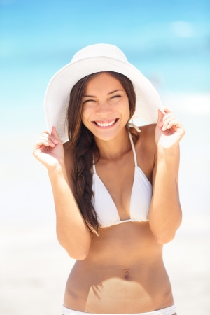 happily: Beach woman happy and playful smiling laughing playful and cheerful in summer sun. Beautiful multiracial Asian Chinese  Caucasian woman wearing white beach hat and bikini. Stock Photo