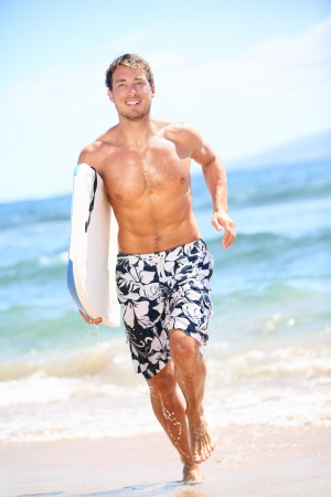 bodyboard: Surfer beach lifestyle people - man surfing running with with bodyboard in water on tropical beach. Fit male fitness model having summer vacation holidays fun on Kaanapali beach, Maui, Hawaii, USA. Stock Photo