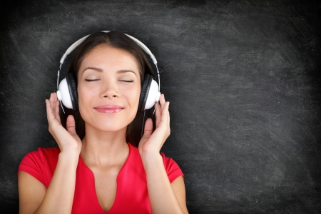 Music in headphones. Beautiful young Asian woman with her eyes closed in bliss listening to music wearing a set of headphones and standing against black blackboard background with copyspace photo