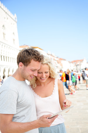 Traveling couple on travel using tablet computer in Venice. Happy young people using travel app looking at map or similar smiling joyful. Young woman and man tourists in their 20s in Italy, Europe. photo