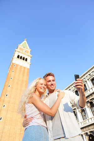 Couple taking selfie picture on travel in Venice in Love. Romantic couple on Piazza San Marco. Young couple on vacation holidays having fun on St Marks Square, Venice, Italy. Beautiful woman and man. photo