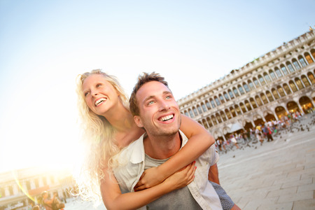 Travel couple in love having fun Venice romance laughing doing piggyback ride in Venice, Italy on Piazza, San Marco. Happy young couple on travel vacation on St Mark's Square. Happy woman and man. photo