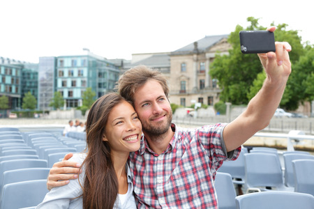 adult cruise: Tourist couple on travel in Berlin, Germany on boat tour cruise smiling happy taking selfie self-portrait photo picture while enjoying their romantic Europe travel vacation. Asian woman, Caucasian man