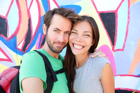 eastern asian: Happy couple selfie selfportrait in front of Berlin Wall, Berlin, Germany. Beautiful young interracial couple looking at camera having fun on Europe travel. Asian woman, Caucasian man. Stock Photo