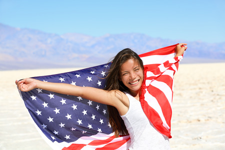 chinese american: Beautiful patriotic vivacious young woman with the American flag held in her outstretched hands standing in the summer sunshine in front of an expanse of white sand and distant mountains