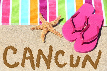 Cancun, Mexico beach travel concept. CANCUN written in sand with water next to beach towel, summer sandals and starfish. Summer and sun vacation holidays. photo