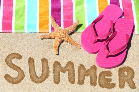 Summer vacation beach travel text concept. SUMMER written in sand with water next to beach towel, summer sandals and starfish. photo