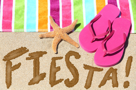 Beach party fiesta travel fun concept. FIESTA written in sand with water next to beach towel, summer sandals and starfish. Summer and sun vacation holidays background. photo
