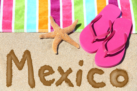 Mexico beach travel concept. MEXICO written in sand with water next to beach towel and summer sandals and starfish. Mexican vacation holidays photo. photo