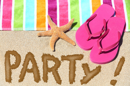 Beach party travel fun concept. PARTY written in sand with\ water next to beach towel, summer sandals and starfish. Summer and\ sun vacation holidays background.