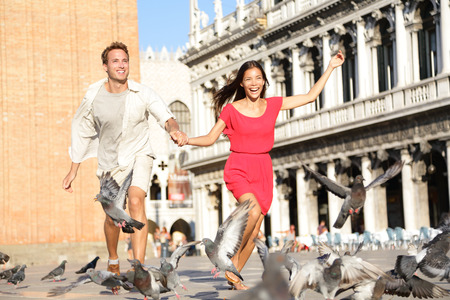 Couple in love having playful fun in Venice holding hands running laughing in Venice, Italy on Piazza, San Marco. Happy young couple on travel vacation on St Marks Square. Happy woman and man. Stock Photo