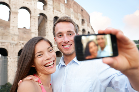 season photos: Happy travel couple taking selife by Coliseum, Rome, Italy. Smiling young romantic couple traveling in Europe taking self portrait photo with smartphone camera in front of Colosseum. Man and woman.
