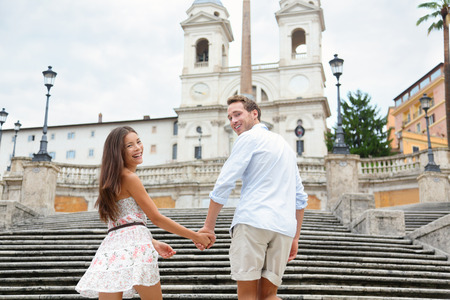 spanish steps: Couple holding hands on Spanish Steps, Rome, Italy. Happy romantic couple. Young interracial couple walking on the travel landmark tourist attraction icon during their romance Europe holiday vacation