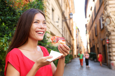 Pizza woman eating pizza slice in Rome, Italy smiling happy outdoors during travel vacation holiday. Beautiful mixed race Asian Caucasian woman enjoying Italian food.