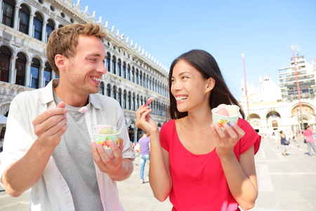 Couple eating ice cream on vacation travel in Venice, Italy. Smiling happy young couple in love having fun eating italian gelato food outdoors during holidays on San Marco Square, Venice, Italy photo
