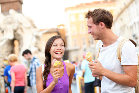 Ice cream - couple eating gelato in Rome on Piazza Navona. Couple eating ice cream on vacation travel in Italy, Europe. Smiling happy young couple in love having fun eating italian food outdoors. Stock Photo