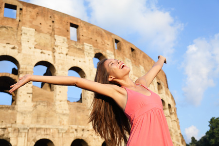 elated: Happy carefree elated travel woman by Colosseum, Rome, Italy with arms raised out and up in ecstatic happiness expression. Travel concept with beautiful mixed race Asian woman in front of Coliseum. Stock Photo