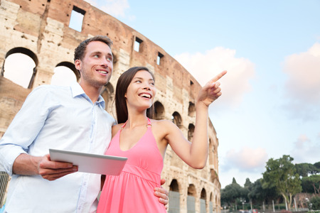 4g: Happy travel couple with tablet by Coliseum, Rome, Italy. Smiling young romantic couple traveling in Europe using tablet pc computer with guidebook or map in front of Colosseum. Man and woman together Stock Photo