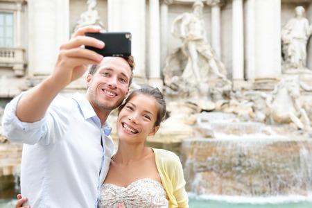 Toeristische paar op reis te nemen selfie foto Trevi Fontein in Rome, Italië. Gelukkig jong romantische paar reizen in Europa nemen zelfportret met smartphone camera. Man en vrouw samen gelukkig Stockfoto