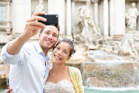italian fountain: Tourist couple on travel taking selfie photo by Trevi Fountain in Rome, Italy. Happy young romantic couple traveling in Europe taking self-portrait with smartphone camera. Man and woman happy together