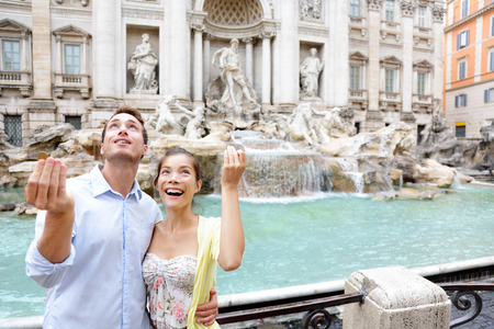 Travel couple trowing coin at Trevi Fountain, Rome, Italy for good luck. Happy young couple smiling traveling together on romantic travel vacation holiday in Europe. Asian woman, Caucasian man.