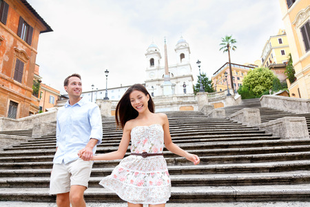 Happy romantic couple holding hands on Spanish Steps in Rome, Italy. Joyful young interracial couple walking on the travel landmark tourist attraction icon during their romance Europe holiday vacation Imagens