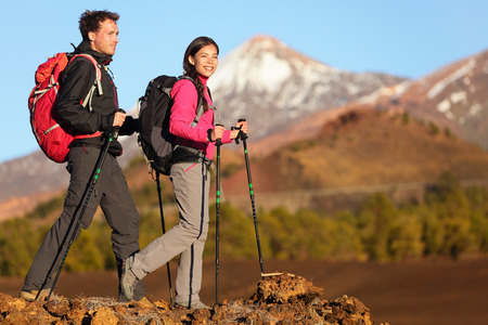 hiking stick: Hikers people hiking - healthy active lifestyle. Hiker people hiking in beautiful mountain nature landscape. Woman and man hikers walking during hike on volcano Teide, Tenerife, Canary Islands, Spain. Stock Photo