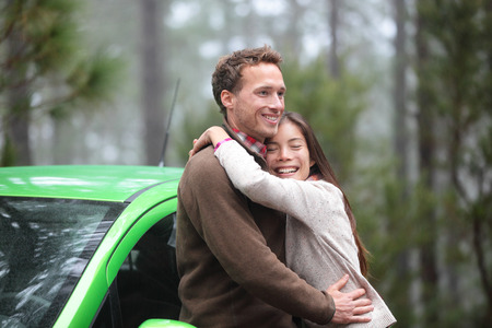 drivers: Couple driving in green car in love on travel. Happy drivers in new rental car on vacation holidays road trip resting in forest embracing and hugging in romance outdoors. Asian woman, Caucasian man.