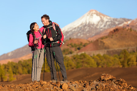 Healthy active lifestyle. Hiker people hiking in beautiful mountain nature landscape. Woman and man hikers laughing resting taking break during hike on volcano Teide, Tenerife, Canary Islands, Spain. photo