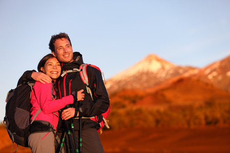Happy couple hiking enjoying looking at view embracing in love. Hiker man and woman wearing backpacks enjoying sunset during hike on mountain volcano Teide, Tenerife, Canary Islands, Spain. photo