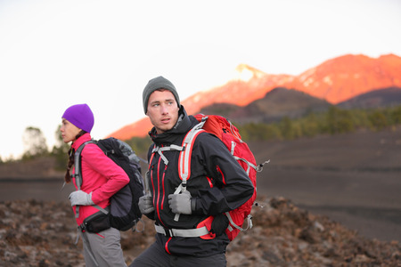 Hiking people on mountain. Hiker couple walking with backpacks outdoors in high altitude. Young man hiker in focus trekking at sunset on volcano Teide, Tenerife, Canary Islands, Spain. photo